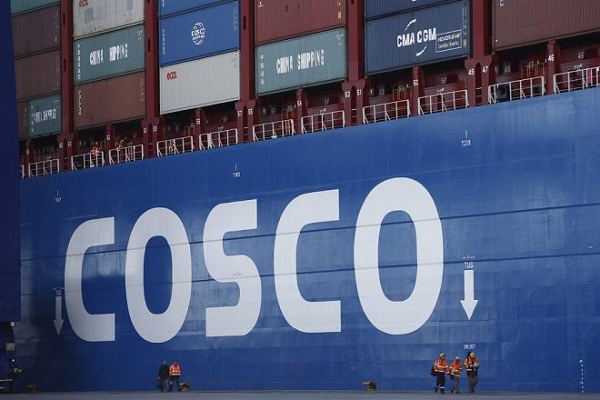 Λιμενεργάτες περπατούν μπροστά από το πλοίο TAURUS, του μεγαλύτερου πλοίου μεταφοράς εμπορευματοκιβωτίων που κατασκευάστηκε ποτέ στην Κίνα, στις εγκαταστάσεις της COSCO PCT στο λιμάνι του Πειραιά, Πειραιάς Δευτέρα 26 Φεβρουαρίου 2018. ΑΠΕ-ΜΠΕ/ΑΠΕ-ΜΠΕ/ΓΙΑΝΝΗΣ ΚΟΛΕΣΙΔΗΣ
