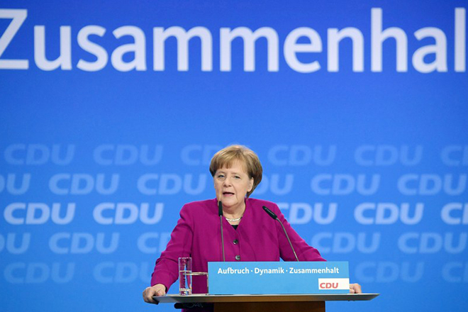 epa06565883 German Chancellor Angela Merkel speaks at the 30th convention of the Christian Democratic Union (CDU) party in Berlin, Germany, 26 February 2018. The party delegates are scheduled to vote on the start of the CDU into a government coalition with the Social Democratic Party (SPD) and the Christian Social Union (CSU). On the previous day, the CDU party leader and German Chancellor Angela Merkel presented her list of candidates for the CDU cabinet members. Part of the slogan in background reads: 'Coherence'.  EPA/CLEMENS BILAN