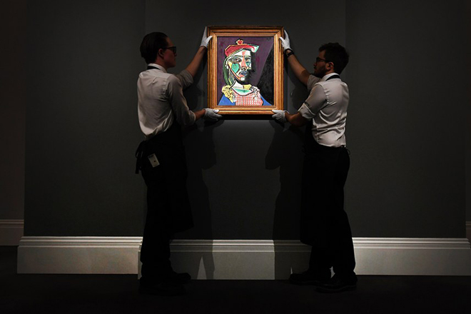 epa06553834 Staff adjust Spanish artist Pablo Picasso's work 'Femme au beret et a la robe quadrillee (Marie-Therese Walter)' at Sotheby's auction house in London, Britain, 22 February 2018. The painting is estimated to fetch 50 million USD at the Impressionist and Modern Art Evening Sale in London on 28 February.  EPA/ANDY RAIN