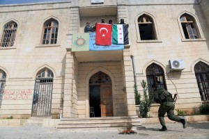 epa06612412 Turkish soldier and Free Syrian Army fighters hold Turkish and Syrian flags at the Kurdish legislative council building after capturing the city of Afrin from Kurdish Popular Protection Units (YPG) forces, northern Syria, 18 March 2018. Turkish President Recep Tayyip Erdogan on 18 March said the Turkish military and allied Syrian militias of the Free Syrian Army had taken complete control of the city of Afrin, the capital of the Kurdish enclave of the same name in northwest Syria.  EPA/AREF TAMMAWI