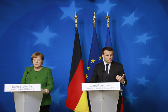 epa06623813 France's President Emmanuel Macron (R) and Germany's Chancellor Angela Merkel (L) attend a news conference after the European Council meeting in Brussels, 23 March 2018. The Spring summit of the European Council was focused on economic and trade affairs.  EPA/OLIVIER HOSLET
