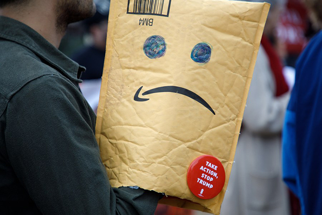 epa06599389 A demonstrator opposed to US president Donald J. Trump holds a modified Amazon package during a protest on the eve of his fundraising visit to Beverly Hills, California, USA, 12 March 2018. Trump is expected to make the fundraising dinner stop after visiting prototypes for his border wall in the San Diego area.  EPA/EUGENE GARCIA
