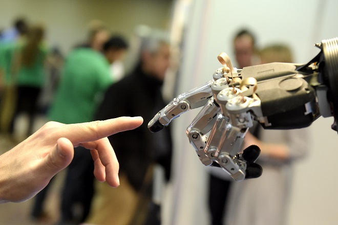 "A man moves his finger toward SVH (Servo Electric 5 Finger Gripping Hand) automated hand made by Schunk during the 2014 IEEE-RAS International Conference on Humanoid Robots in Madrid on November 19, 2014. The conference theme ""Humans and Robots Face-to-Face"" confirms the growing interest in the field of human-humanoid interaction and cooperation, especially during daily life activities in real environments. AFP PHOTO/ GERARD JULIEN        (Photo credit should read GERARD JULIEN/AFP/Getty Images)"