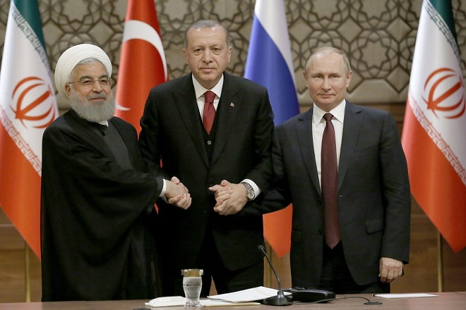epa06645257 Turkish President Recep Tayyip Erdogan (C), Russian President Vladimir Putin (R) and Iranian President Hassan Rouhani (L) shake hands during a press conference after their meeting at the Presidential Palace in Ankara, Turkey, 04 April 2018. Erdogan, Putin and Rouhani are in Ankara for a trilateral meeting on the Syrian crisis.  EPA/TUMAY BERKIN
