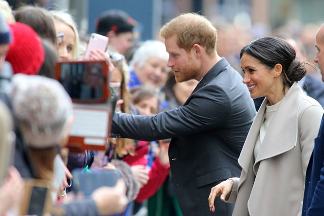 epa06623740 Britain's Prince Harry (C) and US actress Meghan Markle (R) greet spectators as they arrive in Great Victoria Street in Belfast, Northern Ireland, 23 March 2018. Britain's Prince Harry and his fiance came for a one-day visit. The couple met with members of the public who gathered on Great Victoria Street for a walk about and visited the Crown Bar in the city center.  EPA/Paul McErlane
