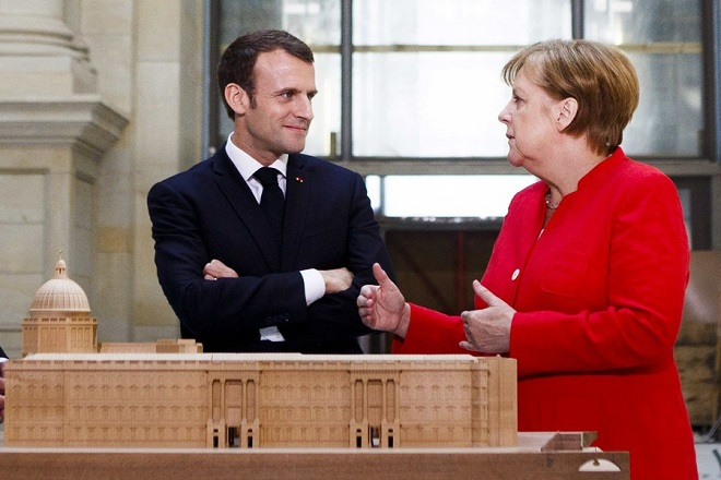 epa06679302 German Chancellor Angela Merkel and French President Emmanuel Macron stay behind a model of the City Palace in the Humboldt Forum cconstruction site in Berlin, Germany, 19 April 2018. The two leaders are meeting following Macron's delivery of an impassioned speech at the European Parliament on 17 April, in which he urged reforms to further bind EU member states together and to counter authoritarianism. The Humboldt Forum, to be located in the reconstructed Berlin City Palace, in German called the Berliner Schloss, will draw on the collections of other Berlin museums and is to become the world's pre-eminent museum dedicated to non-Western art.  EPA/CARSTEN KOALL / POOL