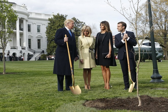 epa06688034 US President Donald J. Trump (L) and First Lady Melania Trump (2R) with French President Emmanuel Macron (R) and his wife Brigitte Macron (2L) as they participate in a tree planting in front of the White House in Washington, DC, USA, 23 April 2018. President Macron will be in DC for three days for a state visit at the White House and an address to a joint session of Congress on 25 April.  EPA/SHAWN THEW