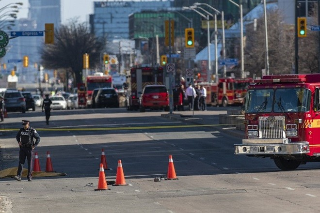 epa06688063 A Toronto police officer stands near a covered body (L) on Yonge Street in Toronto, in northern Toronto, Canada, 23 April 2018. Nine people were killed and 16 injured when a man driving a white van plowed into pedestrians on a sidewalk on a main thoroughfare in Toronto. The man was taken into custody after being confronted by police.  EPA/WARREN TODA