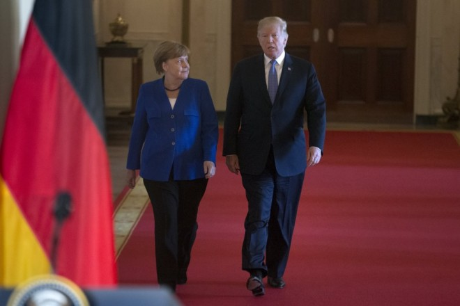 epa06697819 US President Donald J. Trump (R) and Chancellor of Germany Angela Merkel (L) walk down the Crosshall to hold a joint news conference in the East Room of the White House in Washington, DC, USA, 27 April 2018. Merkel is on a one-day working visit to the White House where she and President Trump were expected to discuss trade issues such as proposed US tariffs on European steel and aluminum products, in addition to topics such as NATO.  EPA/MICHAEL REYNOLDS