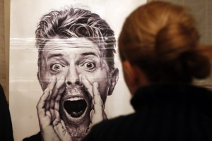 epa05705508 A woman looks at a moving image of late artist David Bowie by Gavin Evans in the former Hansa Studios in Berlin, Germany, 08 January 2017. Bowie recorded some of his most famous songs in the Hansa Studios, which paid tribute to the artist by showing a series of lectures and movies on his 70th birthday. Bowie died 10 January 2016.  EPA/FELIPE TRUEBA