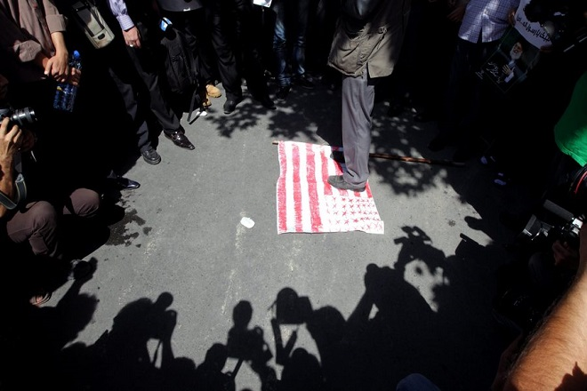 epa03396564 An Iranian Islamist stands on A US flag as some  500 Iranian Islamists gathered in front of the US interest section within the Swiss embassy in Tehran, Iran, on 13 September 2012. Some 500 Reports state that Iranian Islamists gathered to protest against an anti-Islam film made in the US. The Swiss embassy was heavily protected by hundreds of police and anti-riot forces for avoiding any storming of the embassy by the angry Islamists.  EPA/ABEDIN TAHERKENAREH