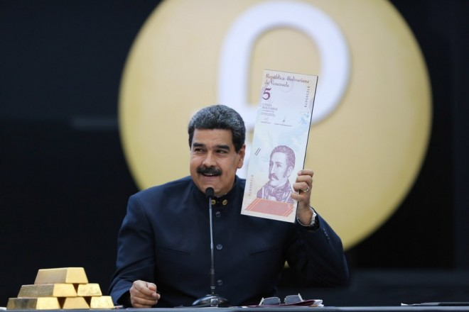epa06622172 A handout photo made available by Miraflores Palace shows Venezuelan President Nicolas Maduro holding an enlarged image of the new five Venezuelan Bolivar note during a press conference in Caracas, Venezuela, 22 March 2018. Maduro ordered the elimination of three zeroes from the Bolivar, the national currency, from 04 June 2018 as part of measures to combat the economic crisis ahead of the snap presidential elections on 20 May 2018.  EPA/MIRAFLORES PRESS HANDOUT  HANDOUT EDITORIAL USE ONLY/NO SALES