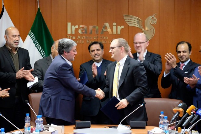 epa05671020 Iran Air Chief Farhard Parwaresh (C-L) and a Boeing regional sales director Fletcher Barkdull (C-R) shake hands after signing a contract to purchase 80 aircraft, as Iran's transport minister Abbas Akhundi (C) looks on, in Tehran, Iran, 11 December 2016. Media reports state Iran's state-owned airline Iran Air and US aircraft manufacturer Boeing have signed a contract to purchase 80 aircraft in contract worth 16.8 billion dollars (15.9 billion euros). The 80 machines - 50 Boeing 737 and 30 Boeing 777 - will be made available to Iran within ten years. The first machine is to be handed over in 2018.  EPA/STRINGER