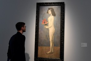 """A man looks at the painting """"Fillette à la corbeille fleurie"""" 1905 by late Spanish painter Pablo Picasso at Christie's France, as part of a presentation of the collection Rockefeller in Paris on March 13, 2018, before the sale at Christie's New York. / AFP PHOTO / BERTRAND GUAY / RESTRICTED TO EDITORIAL USE - MANDATORY MENTION OF THE ARTIST UPON PUBLICATION - TO ILLUSTRATE THE EVENT AS SPECIFIED IN THE CAPTION"""
