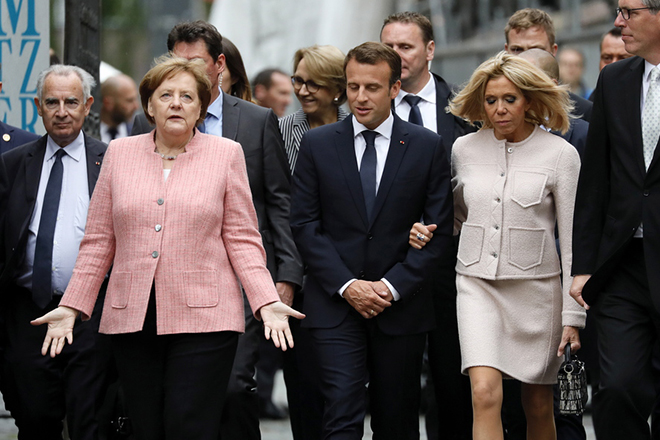 epa06724507 German Chancellor Angela Merkel (L) gestures next to French President Emmanuel Macron (C) and his wife Brigitte Macron (R)  during their arrival for the Charlemagne Prize ceremony at the Cathedral in Aachen, Germany, 10 May 2018. Macron was named to receive the prestigious Charlemagne Prize on 10 May 2018. Annually since 1950, the 'Karlspreis' has been awarded to people who contributed to the unity of Europe and is given by the German city of Aachen.  EPA/RONALD WITTEK
