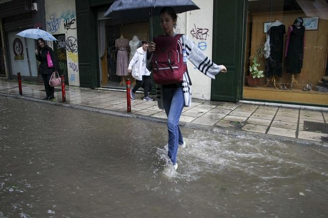 Πολίτες προσπαθούν να διασχίσουν δρόμο με νερά, μετά από την ισχυρή καταιγίδα που έπληξε την πόλη. Θεσσαλονίκη 10 Μαΐου 2018 ΑΠΕ ΜΠΕ/PIXEL