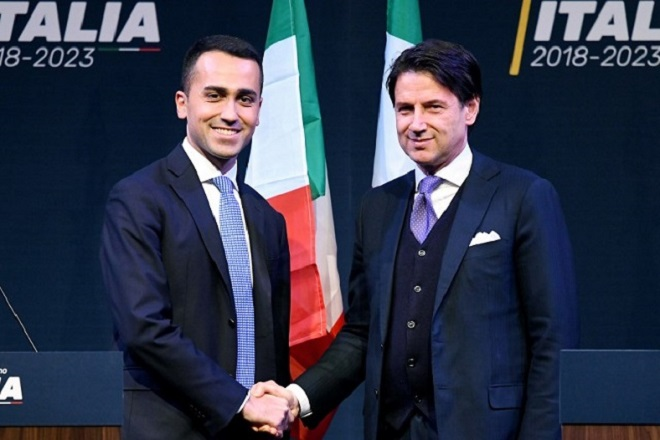 (FILES) In this file photo taken on March 01, 2018 Leader of the Italy's populist Five Star Movement, Luigi Di Maio (L), shakes hands with Italian lawyer Giuseppe Conte, as Di Maio presents his would-be cabinet team. Luigi Di Maio and Matteo Salvini, the leader of the far right party League (Lega) who have reached an agreement on a joint program, have to present their choice to lead the government today on May 21, 2018 and according to the Italian medias Giuseppe Conte could be their candidate. / AFP PHOTO / Filippo MONTEFORTE