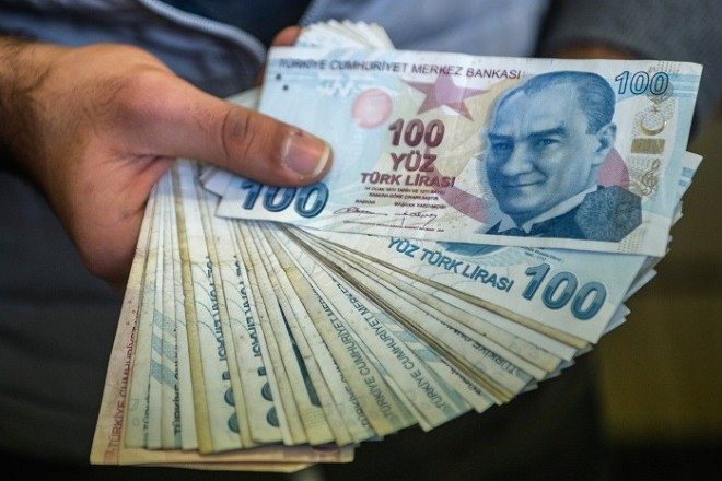A change office staff shows Turkish lira on his hand on December 2, 2016 in Istanbul. Turks have over the past three months nervously watched the steady decline in value of the Turkish lira against the dollar, seeing it haemorrhage more than 10 percent in the past month alone. / AFP PHOTO / OZAN KOSE