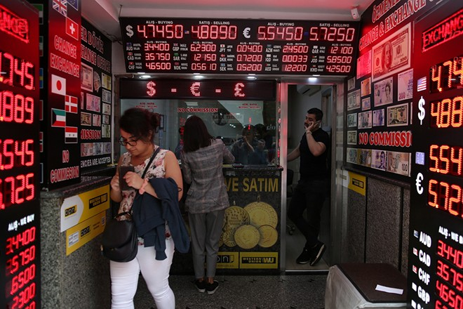 epa06757190 People exchange money at a currency exchange office in Istanbul, Turkey, 23 May 2018. Reports on 23 May state Turkish Lira hit record low against major currencies, recording 4.92 liras against the US dollar and 5.76 liras against the Euro.  EPA/ERDEM SAHIN