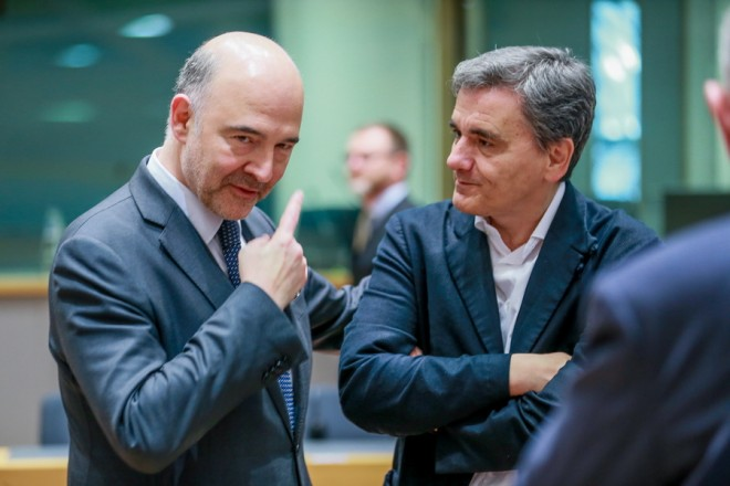 epa06760179 Pierre Moscovici (L), the European Commissioner for Economic and Financial Affairs, Taxation and Customs, and Greek Finance Minister Euclid Tsakalotos (R) chat prior to the start of an Eurogroup Finance Ministers' meeting at the European Council in Brussels, Belgium, 24 May 2018.  EPA/STEPHANIE LECOCQ