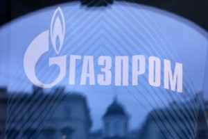 Buildings are reflected in a shop window, as the company logo of Russian natural gas producer Gazprom is seen on a Zenit football club T-shirt, in St. Petersburg, November 14, 2013. Repayments made by Russia's Gazprom to German utility RWE for gas purchases going back to 2010 helped drive earnings at RWE's trading unit 1.3 billion euros ($1.7 billion) higher in the first nine months of this year, RWE said on Thursday. REUTERS/Alexander Demianchuk (RUSSIA - Tags: BUSINESS ENERGY SPORT SOCCER) - RTX15D9S