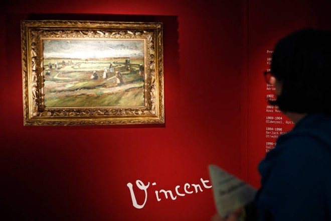 """PARIS, FRANCE - JUNE 04:  A visitor looks at the painting """"Raccommodeuses de filet dans les dunes"""" (Women Mending Nets in the Dunes) by Dutch painter Vincent van Gogh presented by Artcurial auction house in Paris on June 04, 2018 in Paris, France. For the first time in twenty years in Paris, a painting by Van Gogh will be auctioned. It is a youth artwork dated 1882, estimated between 3 and 5 million euros (3,7 and 6,2 millions dollars), the painting will be auctioned off on June 4.  (Photo by Chesnot/Getty Images)"""