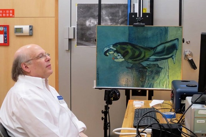 """This handout picture taken on April 18, 2018 and released by Pola Museum of Art on June 5, 2018 shows Washington-based National Gallery of Art researcher John Delaney sitting next to the original painting of """"Mother and Child by the Sea"""" by Spanish painter Pablo Picasso in 1902, during his research at Pola Museum of Art in Hakone, Kanagawa prefecture.                    Infrared imaging technology has helped peel back the layers of a Pablo Picasso painting on display in Japan, and revealed a page from a 1902 newspaper and another composition below. US and Japanese researchers scanned the piece """"Mother and Child by the Sea"""", owned by the Pola Museum of Art in Hakone, west of Tokyo, and uncovered a page of the French newspaper Le Journal from January 18, 1902.  / AFP PHOTO / Pola Museum of Art / Handout / RESTRICTED TO EDITORIAL USE - MANDATORY MENTION OF THE ARTIST UPON PUBLICATION - MANDATORY CREDIT """"AFP PHOTO / Pola Museum of Art"""" -  TO ILLUSTRATE THE EVENT AS SPECIFIED IN THE CAPTION - NO MARKETING NO ADVERTISING CAMPAIGNS NO ARCHIVE - DISTRIBUTED AS A SERVICE TO CLIENTS /"""