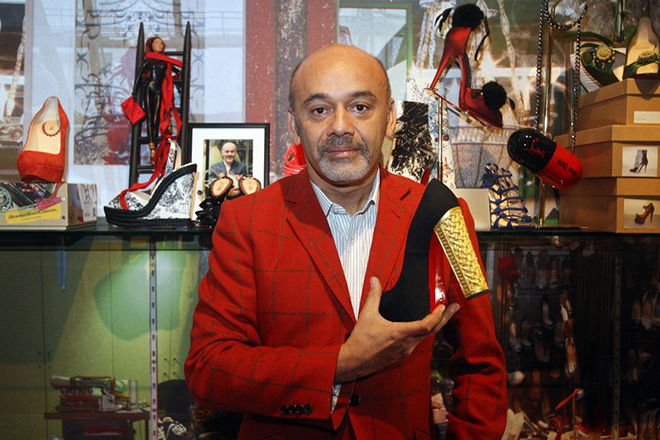 epa03201556 French footwear designer Christian Louboutin poses for the photographer holding one of his shoes at the exhibition celebrating 20 years of the famous red soled footwear brand at the Design Museum, London, Britain, 30 April 2012.  EPA/Lewis Whyld UK and Republic of Ireland Out, no commercial sales  EDITORIAL USE ONLY