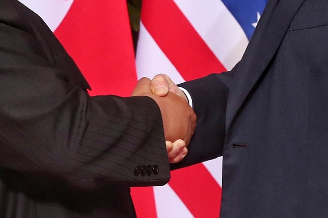 epaselect epa06801618 US President Donald J. Trump (R) and North Korean leader Kim Jong-un (L) shake hands at the start of a historic summit at the Capella Hotel on Sentosa Island, Singapore, 12 June 2018. The summit marks the first meeting between an incumbent US President and a North Korean leader.  EPA/KEVIN LIM / THE STRAITS TIMES / SPH SINGAPORE OUT    EDITORIAL USE ONLY  EDITORIAL USE ONLY