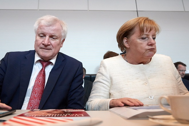 epaselect epa06802486 Minister of Interior, Construction and Homeland Horst Seehofer (L) of the Christian Social Union (CSU) and German Chancellor Angela Merkel (R) of the Christian Democratic Union (CDU) during the beginning of a faction meeting in Berlin, Germany, 12 June 2018.  EPA/HAYOUNG JEON