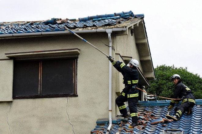 epa06817598 Firefighters try to remove debris on the damaged roof of a house, after a magnitude 6.1 earthquake in Osaka, western Japan, 18 June 2018. The earthquake, which struck western Japan, killed three people injured more than 50.  EPA/JIJI PRESS EDITORIAL USE ONLY/NO ARCHIVE/JAPAN OUT  EDITORIAL USE ONLY  EDITORIAL USE ONLY
