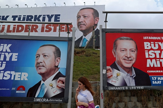 epa06818624 A woman pass in front of huge pictures of Turkish President Recep Tayyip Erdogan in Istanbul, Turkey, 18 June 2018. Turkish President Erdogan announced on 18 April that Turkey will hold snap presidential and parliamentary elections on 24 June 2018, after elections were scheduled to be held in November 2019.  EPA/ERDEM SAHIN