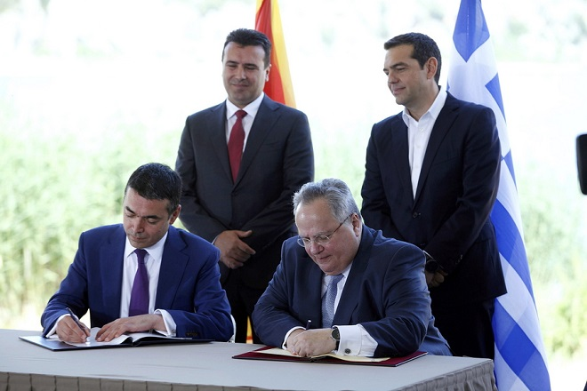 epa06814994 Greek Prime Minister Alexis Tsipras (back- R) and FYROM Prime Minister Zoran Zaev (back- L) watch foreign ministers of Greece, Nikos Kotzias (front- R) and Former Yugoslav Republic of Macedonia (FYROM), Nikola Dimitrov (front- L) signing an agreement in the village of Psarades, Florina, Greece, 17 June 2018. The foreign ministers of Greece and the Former Yugoslav Republic of Macedonia (FYROM), Nikos Kotzias and Nikola Dimitrov, and the UN Secretary General's Special Envoy for the name dispute signed a historic agreement on 17 June 2018 for resolving the decades-long issue during a lakeside signing ceremony in Prespes, where the borders of Greece, FYROM and Albania meet.  EPA/NIKOS ARVANITIDIS