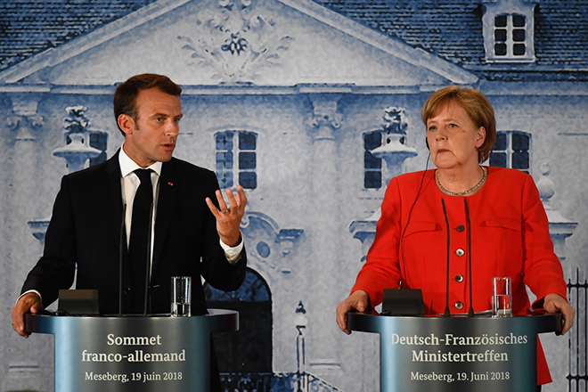epa06821368 German Chancellor Angela Merkel (R) and French President Emmanuel Macron attend a press conference during the German-French Minister Meeting in front of the German government's guest house Meseberg Palace in Meseberg, near Berlin, Germany, 19 June 2018. German and French ministers meet for an one day meeting to discuss bilateral topics, including Foreign, Defence and Security politics.  EPA/FILIP SINGER