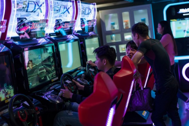 epa06619229 A group of men play video games at a game arcade in Shenzhen, Guangdong Province, China, 21 March 2018 (issued 22 March 2018). Game arcades are a popular pastime in Shenzhen.  EPA/STR