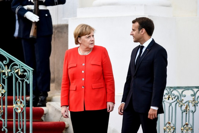 epa06822277 German Chancellor Angela Merkel (L) talks with French President Emmanuel Macron  during the German-French Minister Meeting in front of the German government's guest house Meseberg Palace in Meseberg, near Berlin, Germany, 19 June 2018. German and French ministers meet for a one day meeting to discuss bilateral topics, including Foreign, Defence and Security politics.  EPA/FILIP SINGER