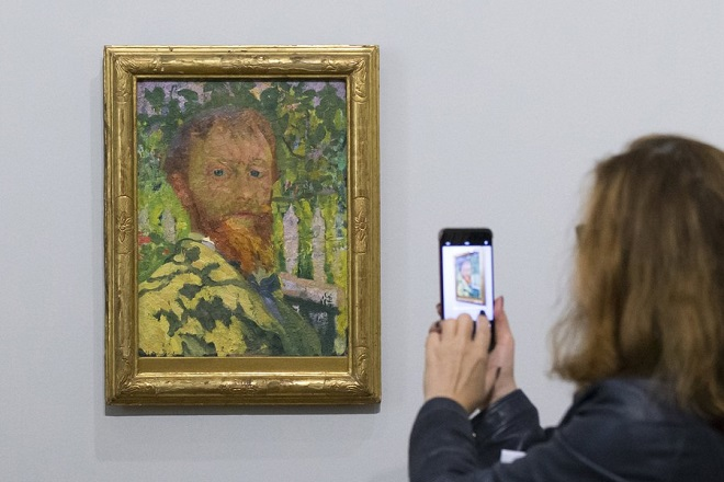 epa06133568 A visitor takes a picture of the painting 'Selbstportrait' (Self portrait) by Swiss artist Giovanni Giacometti, on display as part of the art exhibition 'Desire makes everything blossom… Van Gogh to Cezanne, Bonnard to Matisse. The Collection Hahnloser' at the Kunstmuseum (Museum of Fine Arts) in Bern, Switzerland, 09 August 2017. The show presenting artworks from the Hahnloser Collection opens to the public from 11 August 2017 to 11 March 2018.  EPA/PETER KLAUNZER