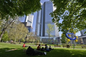 epa06679821 People enjoy a lunch break in the shadows cast by trees, with the office tower of European Banking Authority (EBA) at right and Commerzbank headquarters at left on background in Frankfurt am Main, Germany, 19 April 2018.  EPA/MAURITZ ANTIN