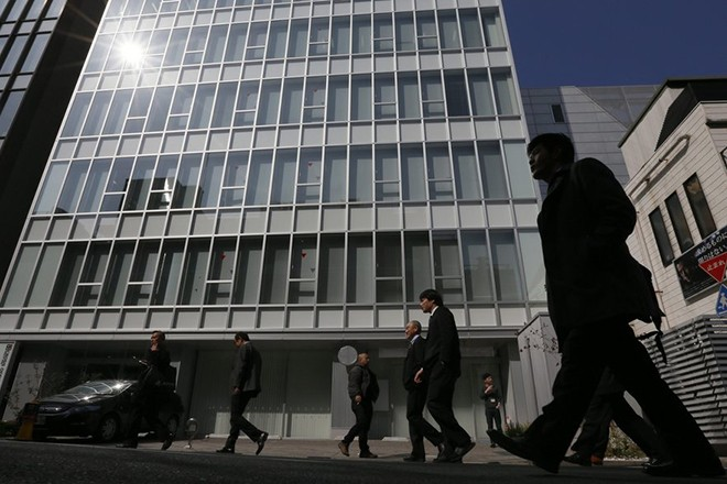epa04100685 Office workers walk past a multi-tenant building, where Mt. Gox, a big bitcoin exchange is based in Tokyo, Japan, 26 February 2014. Mt. Gox said on its website it has halted all transactions for an indefinite period to protect its site and users.  EPA/KIMIMASA MAYAMA