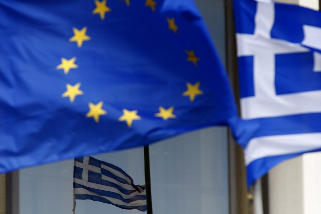 Greek and EU flags are seen outside the Foreign Ministry in Athens March 12, 2015. Greece has lost a lot of trust and euro zone governments must decide whether to expand their risk exposure to Athens, European Central Bank policymaker Jens Weidmann said on Thursday. REUTERS/Yannis Behrakis (GREECE - Tags: POLITICS BUSINESS)