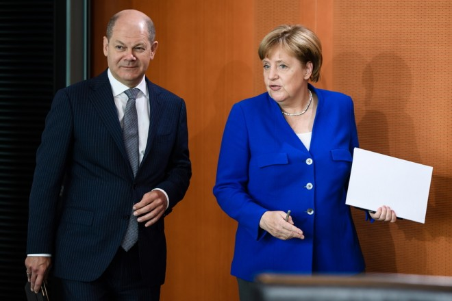 epa06879772 German Chancellor Angela Merkel (R) and German Minister of Finance Olaf Scholz (L) arrive for the beginning of the weekly cabinet meeting in Berlin, Germany, 11 July 2018. During the 17th cabinet meeting, the ministers and the Chancellor are expected to discuss, among others, a draft law on an international agreement on the secure and environment friendly recycling of ships.  EPA/CLEMENS BILAN