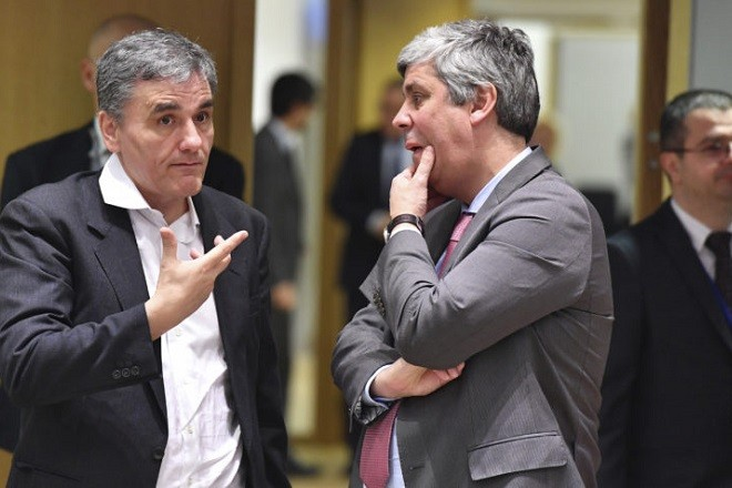 Eurogroup President Mario Centeno, right, speaks with Greek Finance Minister Euclid Tsakalotos during a meeting of the eurogroup in extended format at the EU Council building in Brussels on Monday, Feb. 19, 2018. Ireland is withdrawing its candidate, Philip Lane, for European Central Bank vice president, making it almost certain that Spain's finance minister, Luis de Guindos, will get the job. (AP Photo/Geert Vanden Wijngaert)