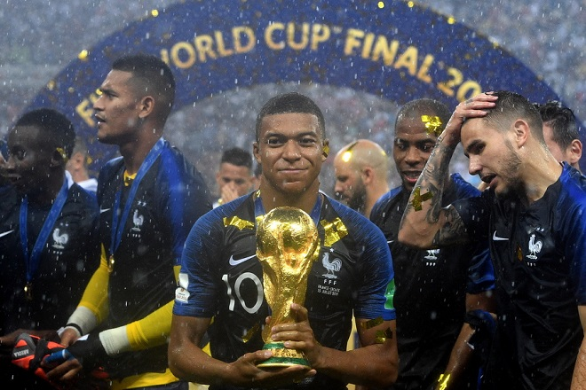 epaselect epa06891526 Kylian Mbappe of France reacts with the trophy after winning the FIFA World Cup 2018 final between France and Croatia in Moscow, Russia, 15 July 2018.  (RESTRICTIONS APPLY: Editorial Use Only, not used in association with any commercial entity - Images must not be used in any form of alert service or push service of any kind including via mobile alert services, downloads to mobile devices or MMS messaging - Images must appear as still images and must not emulate match action video footage - No alteration is made to, and no text or image is superimposed over, any published image which: (a) intentionally obscures or removes a sponsor identification image; or (b) adds or overlays the commercial identification of any third party which is not officially associated with the FIFA World Cup)  EPA/FACUNDO ARRIZABALAGA   EDITORIAL USE ONLY