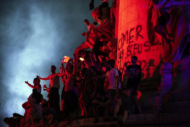 epa06892094 French supporters celebrate on the Place de la Republique after France won during the FIFA World Cup 2018 final match between France and Croatia in Paris, France, 15 July 2018. On the statue is written 'Thank you the blue'  EPA/ETIENNE LAURENT