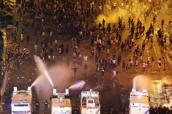 epa06892153 French riot police uses water cannon trucks to disperse people on Champs-Elysees avenue after French supporters celebrated the victory of France at the FIFA World Cup 2018 final match against Croatia in Paris, France, 15 July 2018.  EPA/GUILLAUME HORCAJUELO