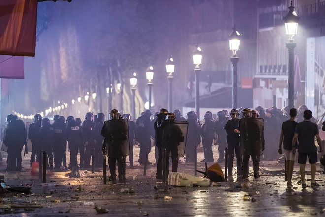 epa06892165 French riot police disperse people on Champs-Elysees avenue after French supporters celebrated the victory of France at the FIFA World Cup 2018 final match against Croatia in Paris, France, 15 July 2018.  EPA/IAN LANGSDON