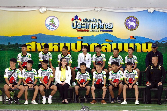 epaselect epa06896312 Twelve rescued members of the Wild Boar soccer team and their assistant coach sit with Thai health officers and soldiers to make their first public appearance during a military governmental TV pool broadcasting program at Chiang Rai Provincial Administrative Organization in Chiang Rai province, Thailand, 18 July 2018. The thirteen members of Wild Boar child soccer team, including their assistant coach, who were trapped in the Tham Luang cave since 23 June 2018, made their first appearance on the day for a tightly-controlled interview with the media after they were rescued, before returning to their homes with families.  EPA/PONGMANAT TASIRI