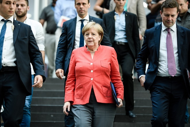 epa06899969 German Chancellor Angela Merkel (C) leaves after her annual press conference at 'Bundespressekonferenz' in Berlin, Germany, 20 July 2018. The traditional media briefing usually takes place during summer time.  EPA/CLEMENS BILAN