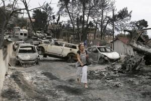 Κάτοικος περνάει δίπλα από καμένα αυτοκίνητα στο Μάτι, Τρίτη 24  Ιουλίου 2018. Σε κατάσταση έκτακτης ανάγκης κηρύχθηκαν οι περιφερειακές ενότητες της Ανατολικής και Δυτικής Αττικής μετά τις πυρκαγιές που έπληξαν τις περιοχές. ΑΠΕ-ΜΠΕ/ΑΠΕ-ΜΠΕ/ΓΙΑΝΝΗΣ ΚΟΛΕΣΙΔΗΣ