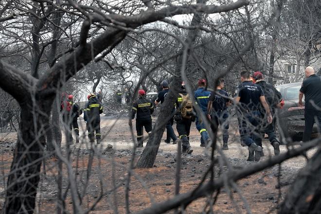 Πυροσβέστες ερευνούν την περιοχή όπου βρέθηκαν 26 απανθρακωμένα πτώματα σε χωράφι στην Αργυρά Ακτή στο Μάτι, Τρίτη 24 Ιουλίου 2018. Απανθρακωμένα πτώματα βρέθηκαν σε χωράφι,  σε απόσταση περίπου 15 μέτρων από τη θάλασσα. Στην περιοχή δεν υπάρχει ακτή αλλά βράχια, γεγονός που δείχνει ότι οι άνθρωποι που πρέπει να επιχείρησαν να βρουν διέξοδο στη θάλασσα, εγκλωβίστηκαν με αποτέλεσμα να χάσουν τη ζωή τους μέσα στις φλόγες. ΑΠΕ-ΜΠΕ/ΑΠΕ-ΜΠΕ/ΠΑΝΤΕΛΗΣ ΣΑΪΤΑΣ